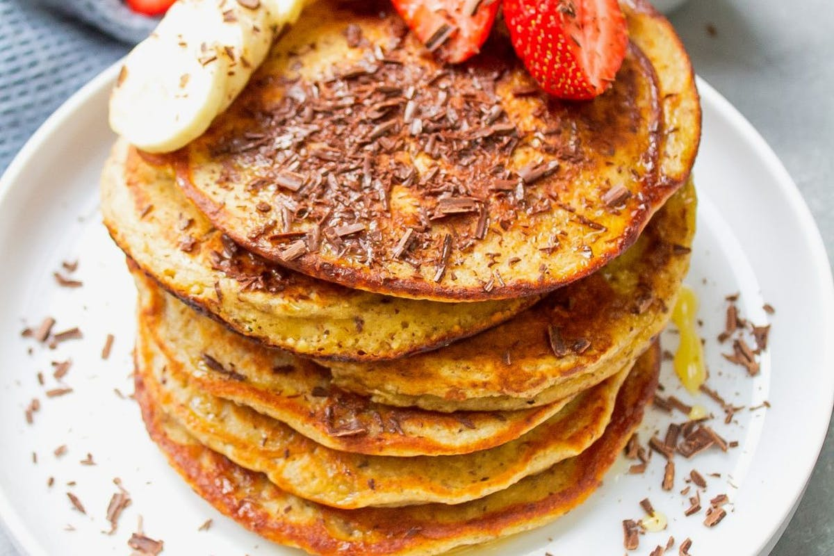Banana and oat pancakes stacked on a plate with chocolate shakings, strawberries and banana on top