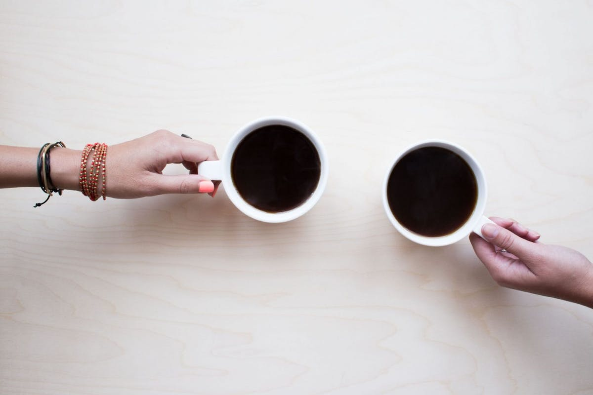 Two mugs of coffee with hands on the handle