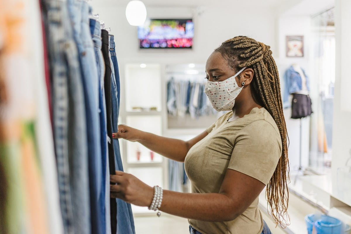 A woman looking at a rack of clothing in a shop with a mask on