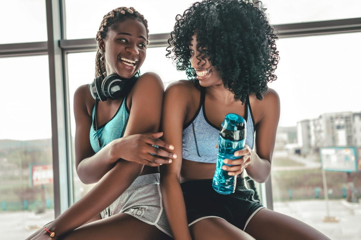 Two women wearing shorts and sports bras laugh at the gym.