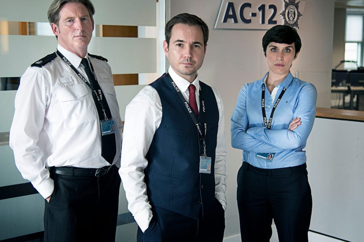 Three Line of Duty actors as police officers from BBC show Line of Duty stood in front of their office