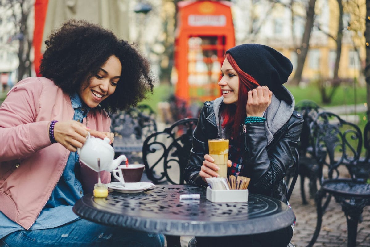 Two women drinking coffee outside at a cafe