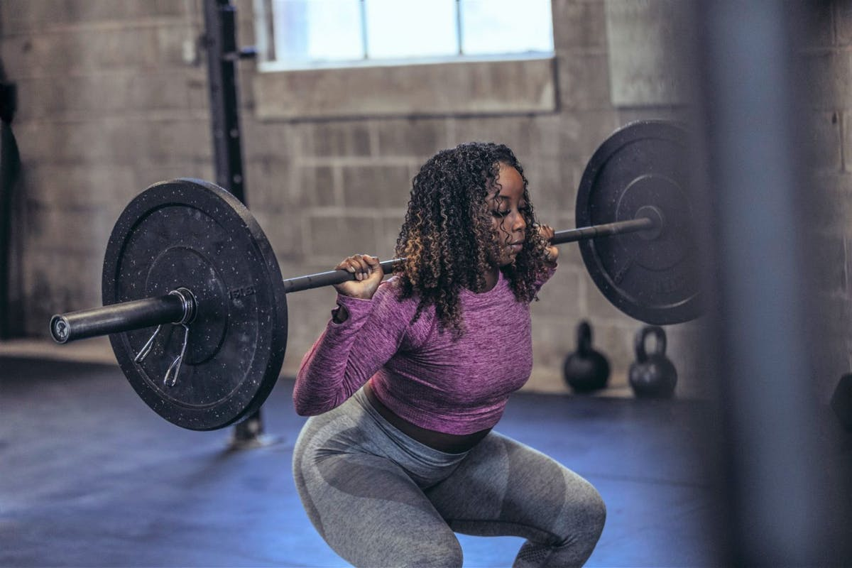 A woman doing a squat in the gym with a barbell on her back.