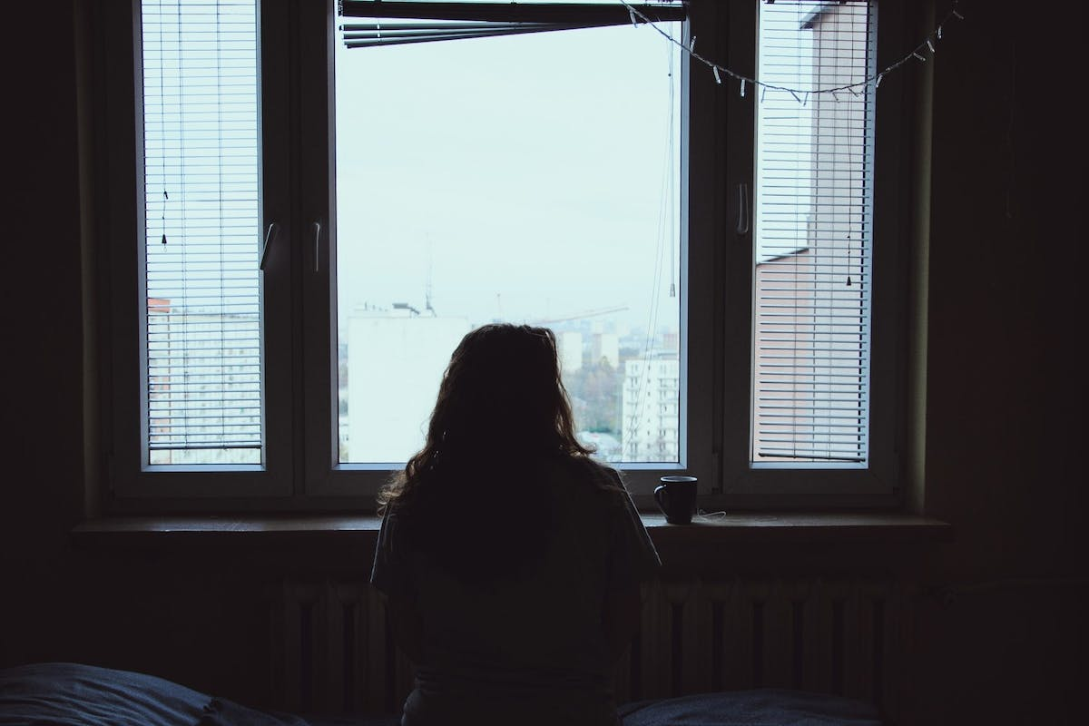 Rear view of a woman looking out of a window