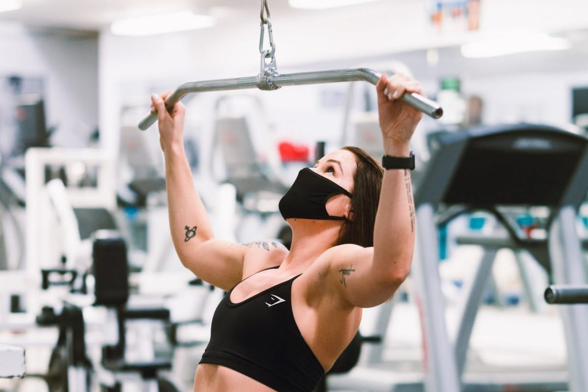A woman using the lat pull down machine while exercising in the gym.