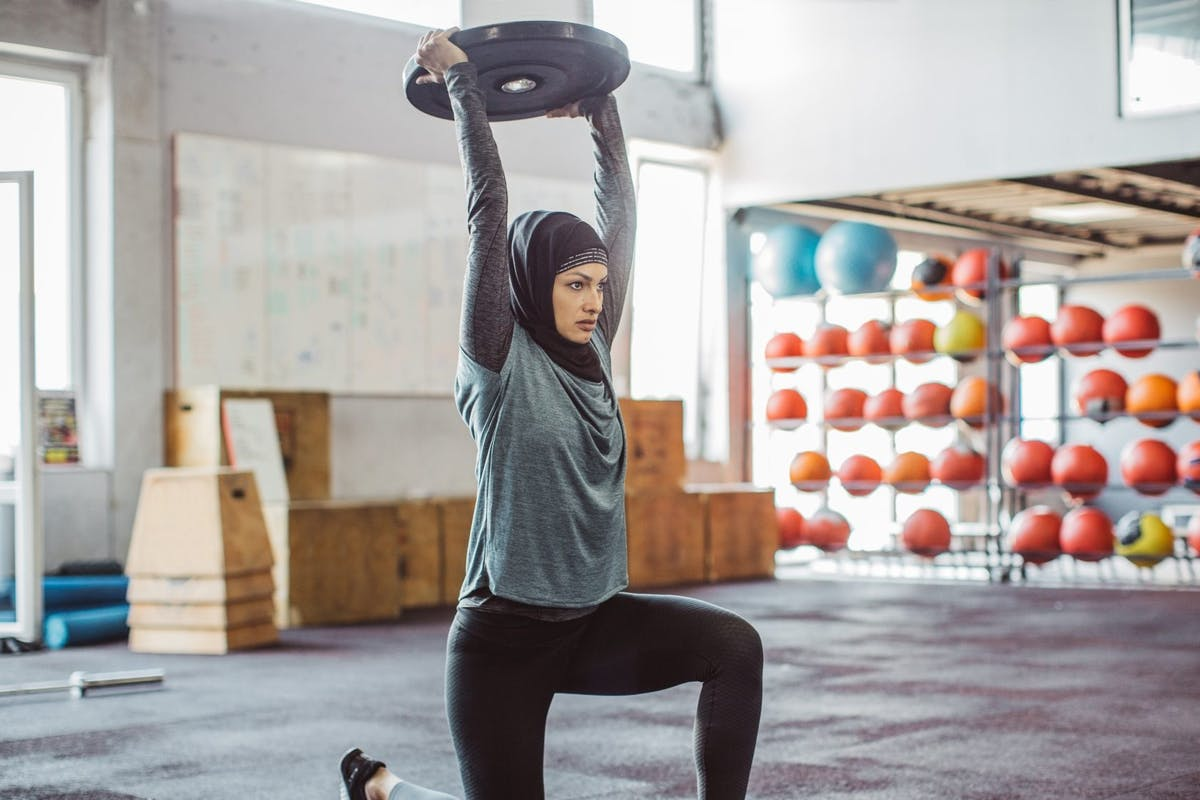 woman lifting weight above her head in gym