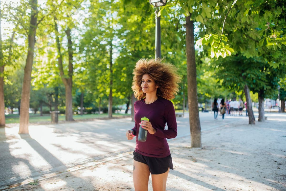 A happy woman running in an urban park.