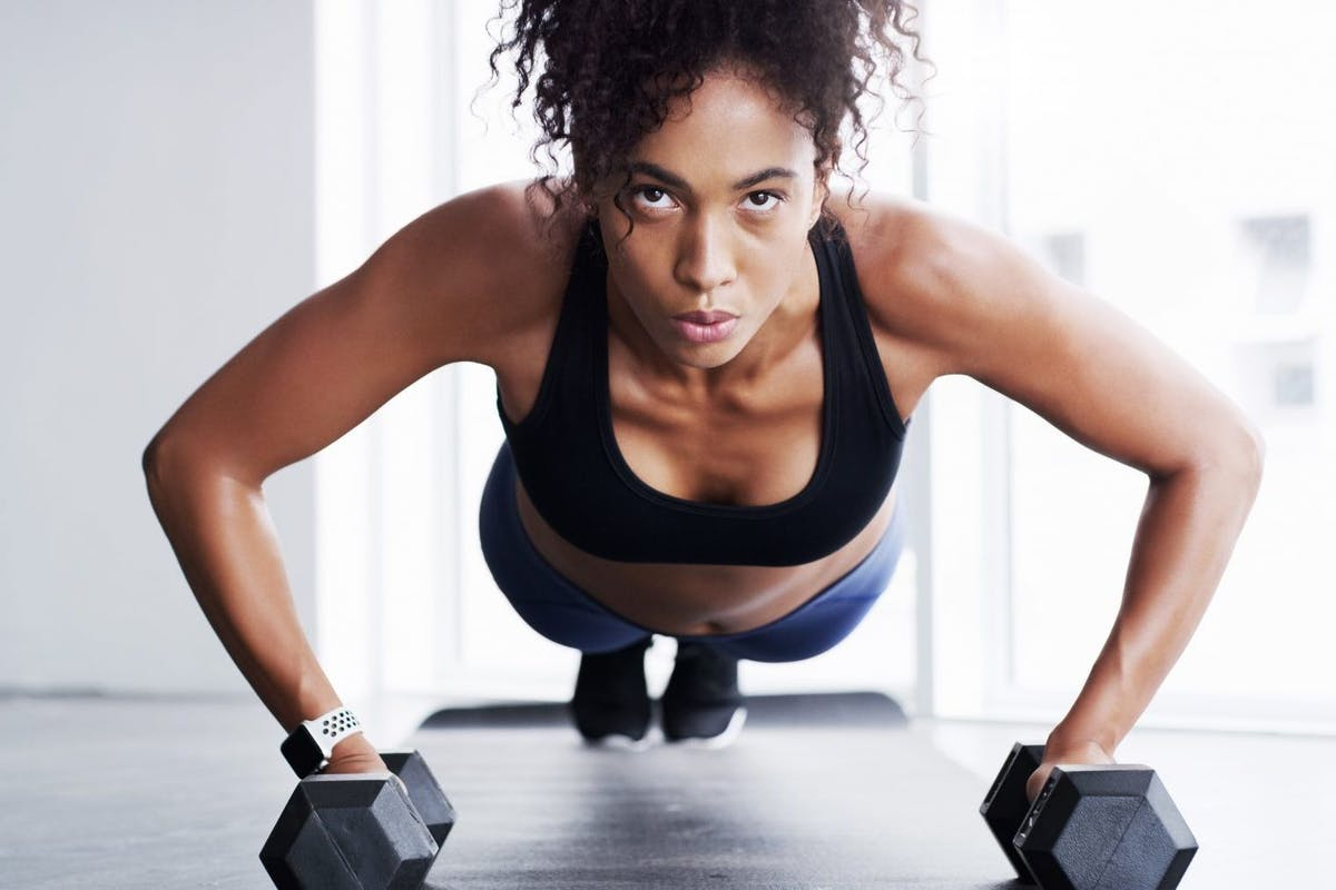Woman planking with dumbbells