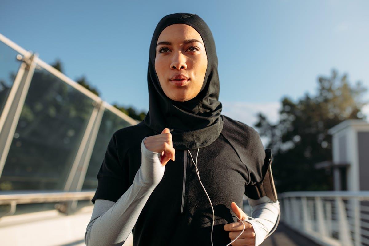 A woman running through an urban street with headphones on.