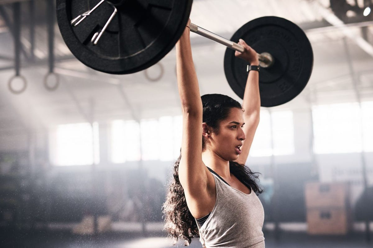 A woman lifting a barbell overhead in the gym.