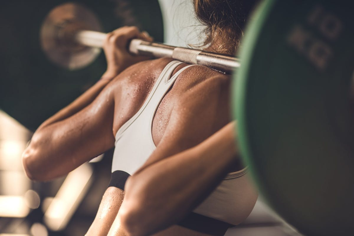 Woman lifting a barbell with weights on it