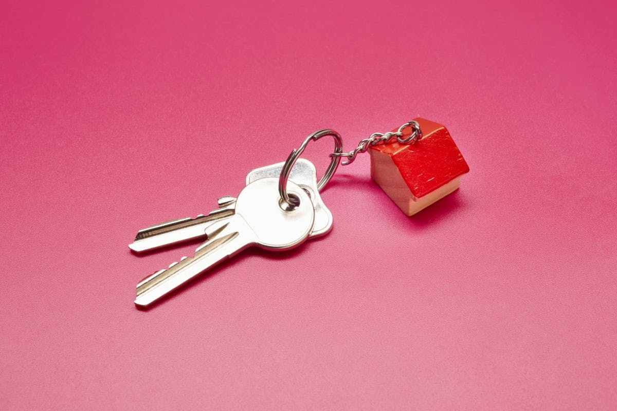 A pair of house keys on a pink background