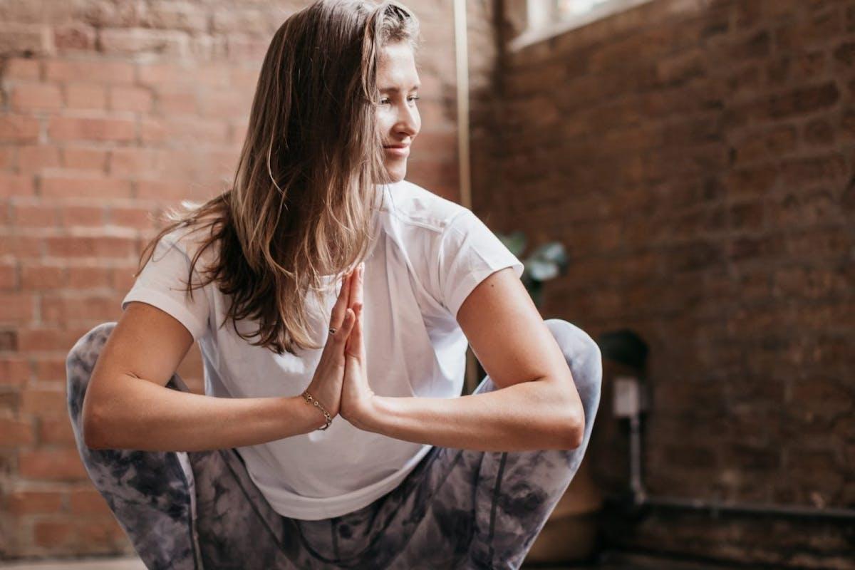 Annie Clarke, yoga teacher, sits in malasana aka yogi squat to open her hips.