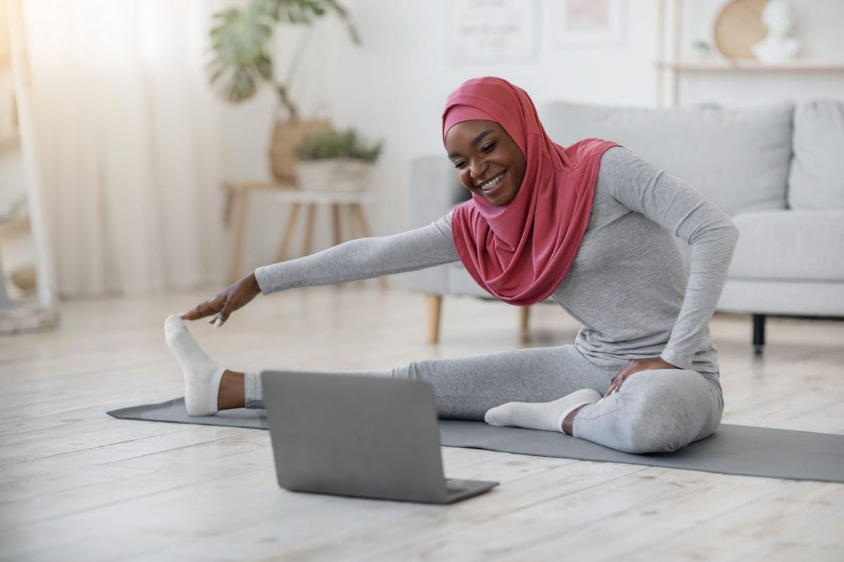 Hijab wearing woman doing pilates at home