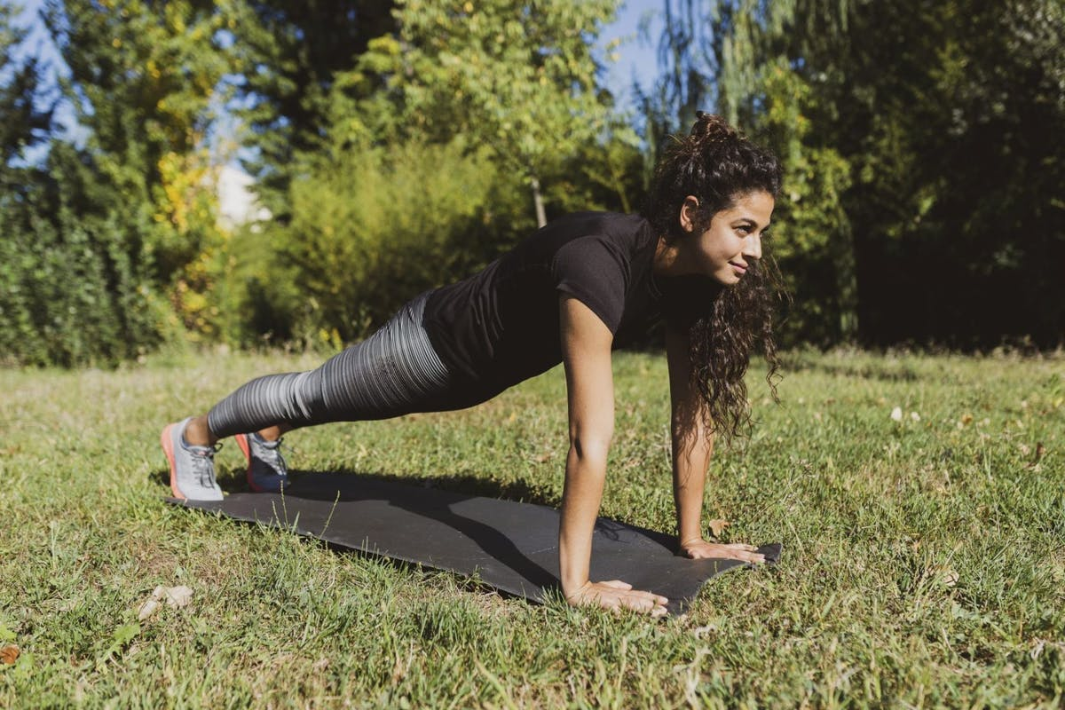 Woman doing a push up outside