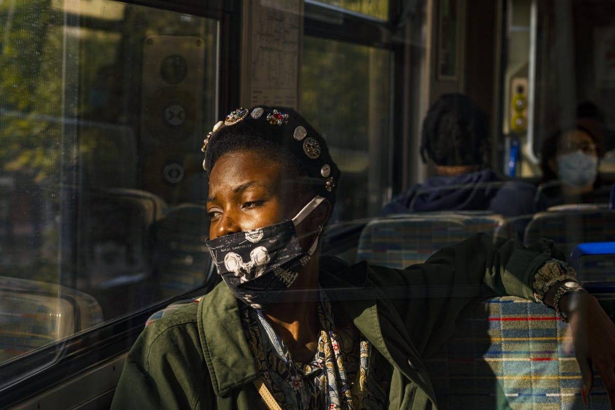 Woman on a bus wearing a face mask looking out of the window