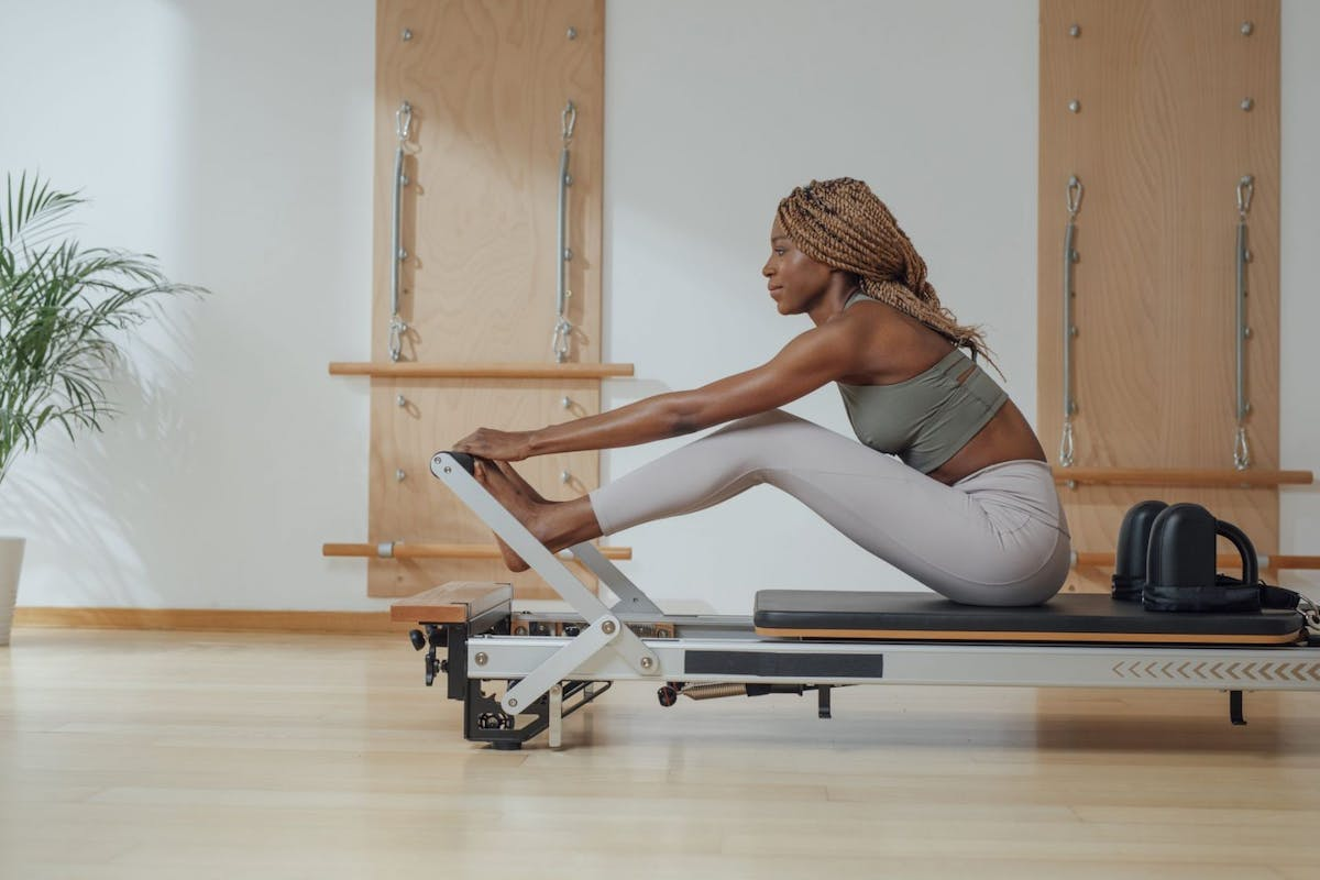 A woman sat on a reformer machine about to do reformer pilates in a workout studio