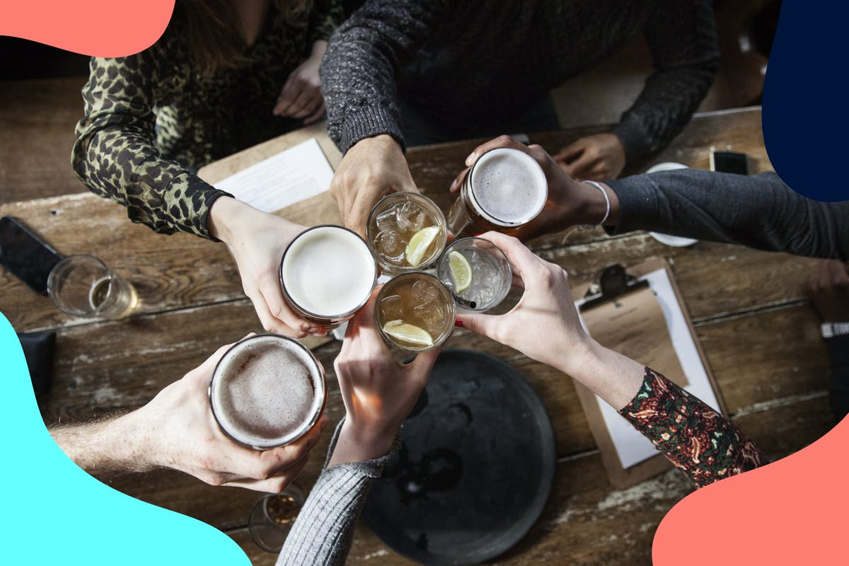 group of friends cheersing alcoholic drinks socialising at a pub