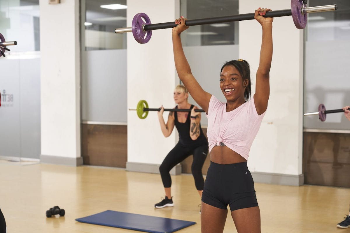 Three women training in a sports hall during an exercise class.