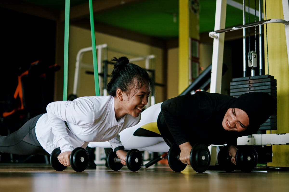 Two women in the gym doing a press up on dumbbells