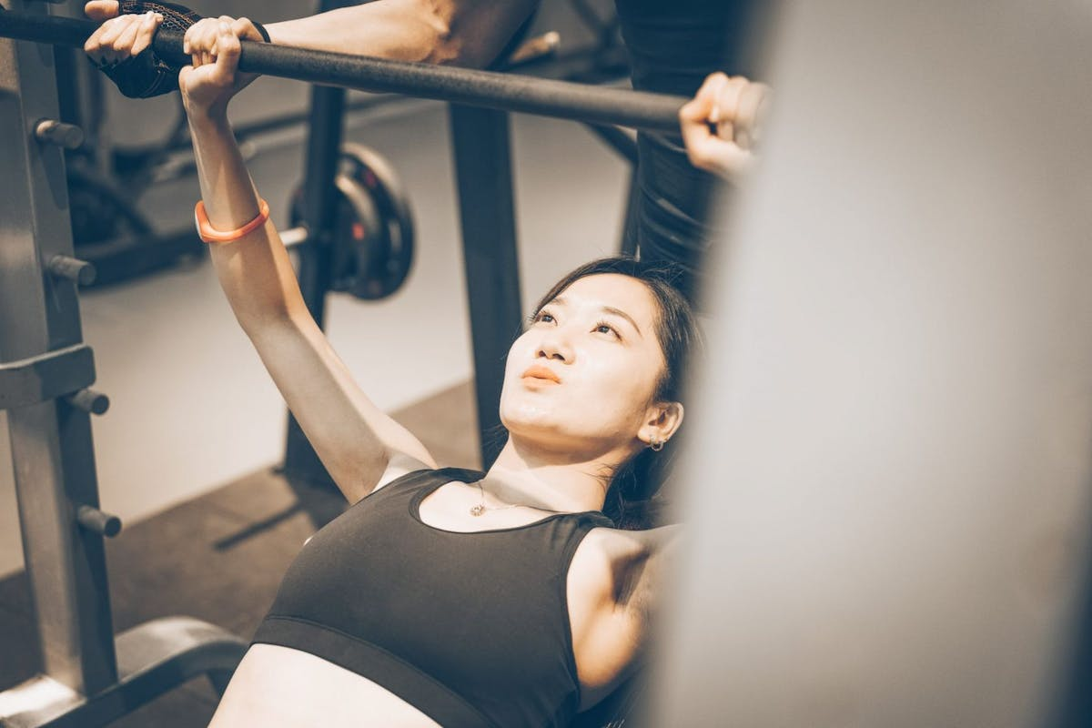 A woman doing a bench press during a push workout at the gym.