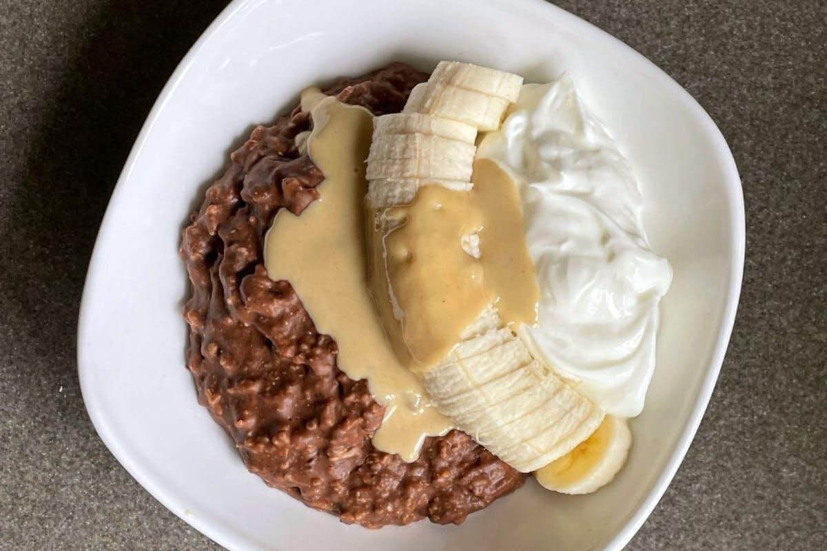 A bowl of chocolate tahini protein porridge with sliced banana and Greek yoghurt.