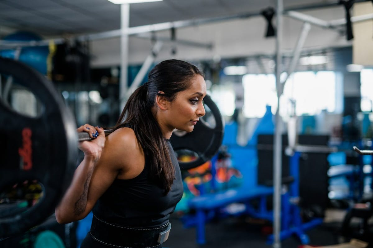 Poorna Bell with a barbell on her back in the weights room of a gym about to squat.