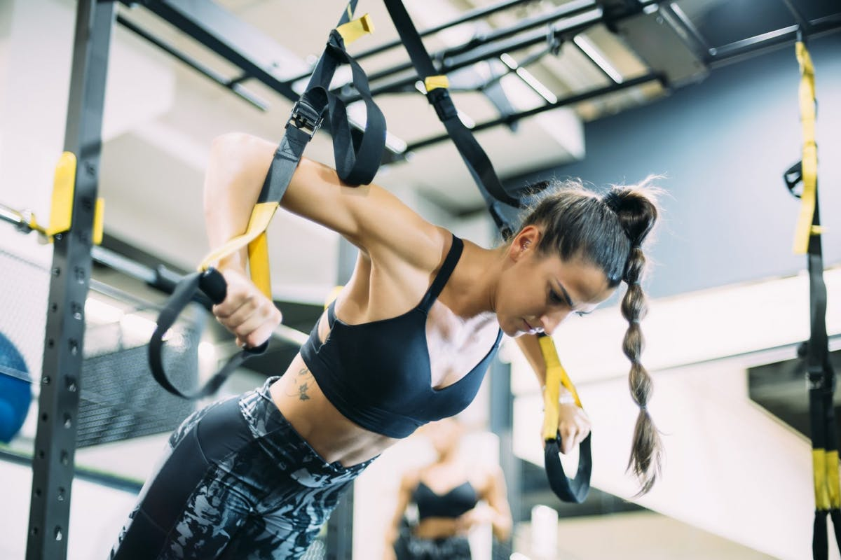woman doing suspension traning in the gym with TRX bands