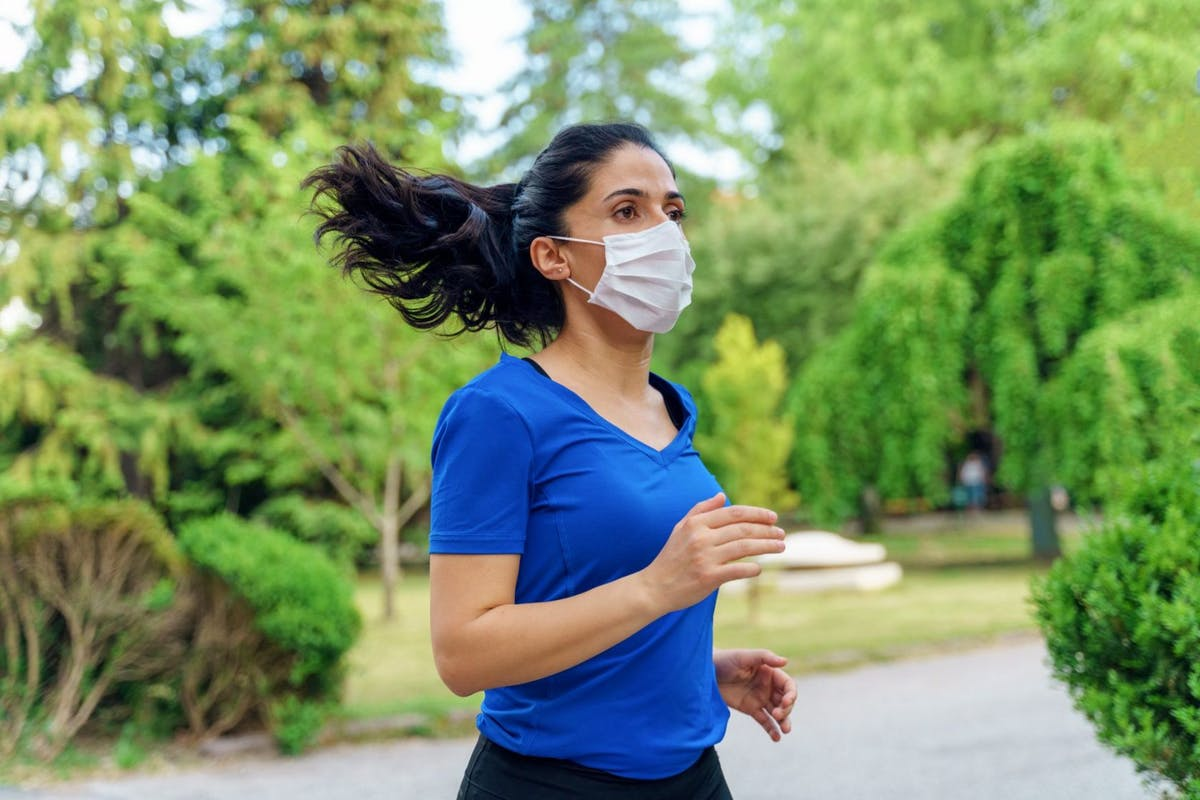 A woman running through a park in a pink facemask