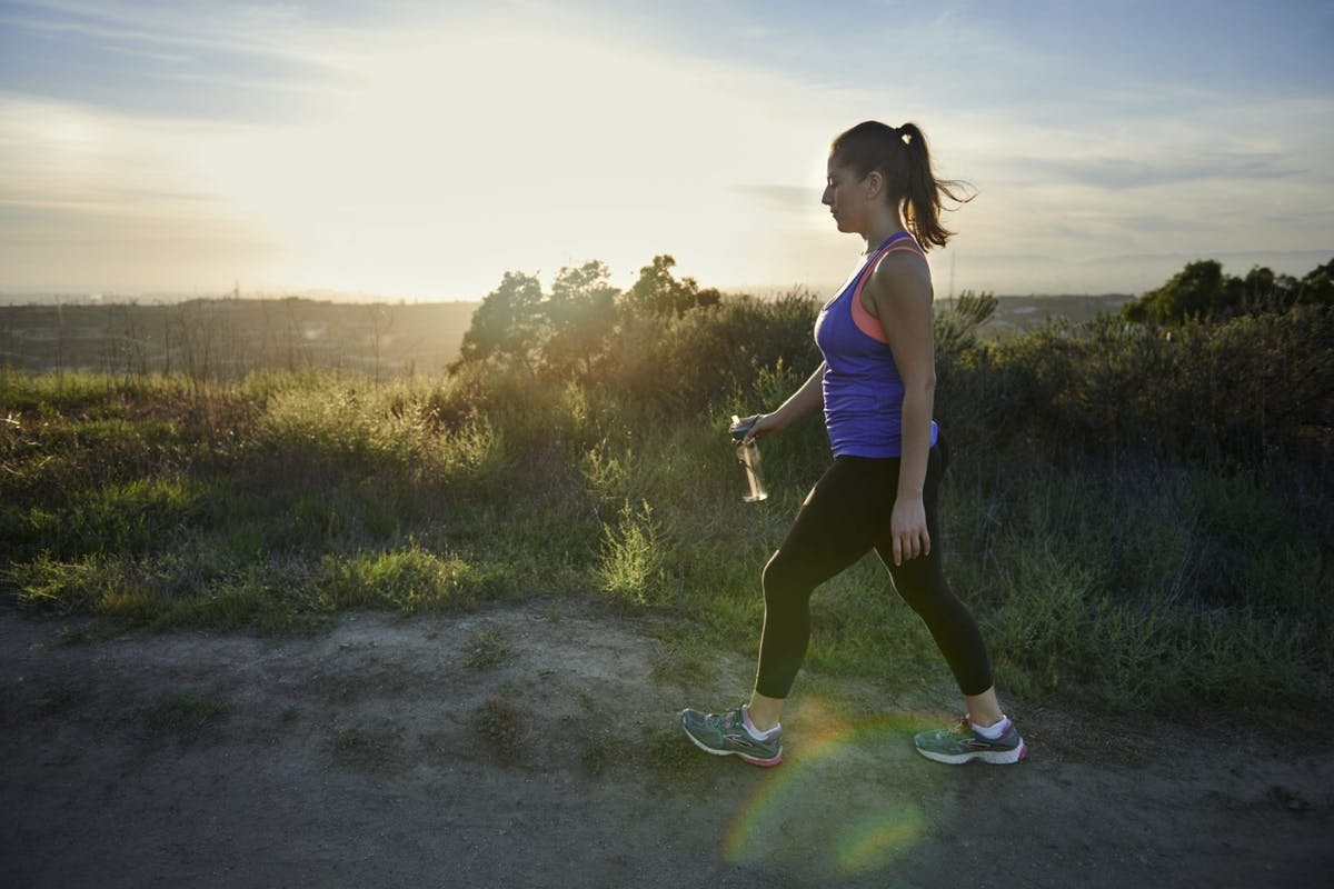 A woman walking through a hilly rural area in a vest top, leggings and trainers.