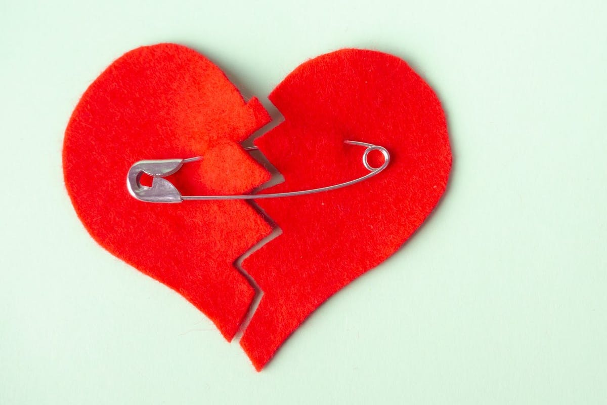 A broken heart held together with a safety pin