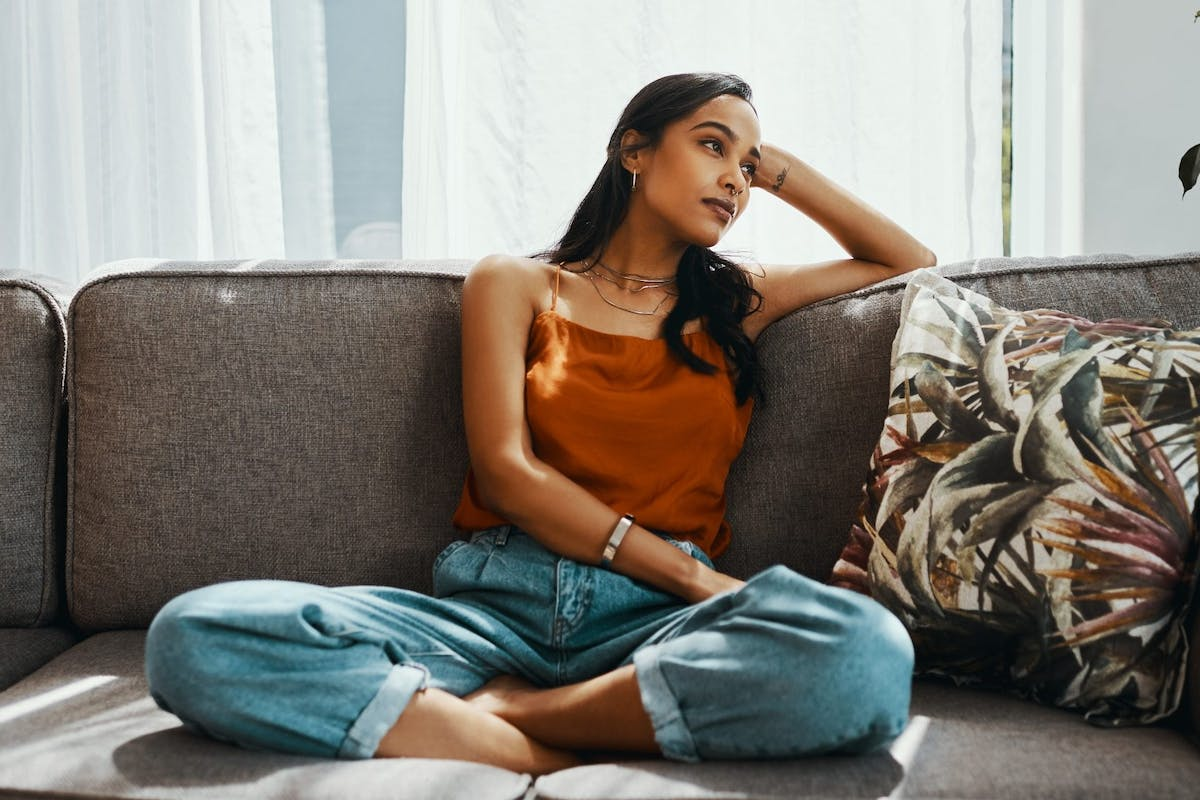 Woman sitting on sofa looking bored and unmotivated