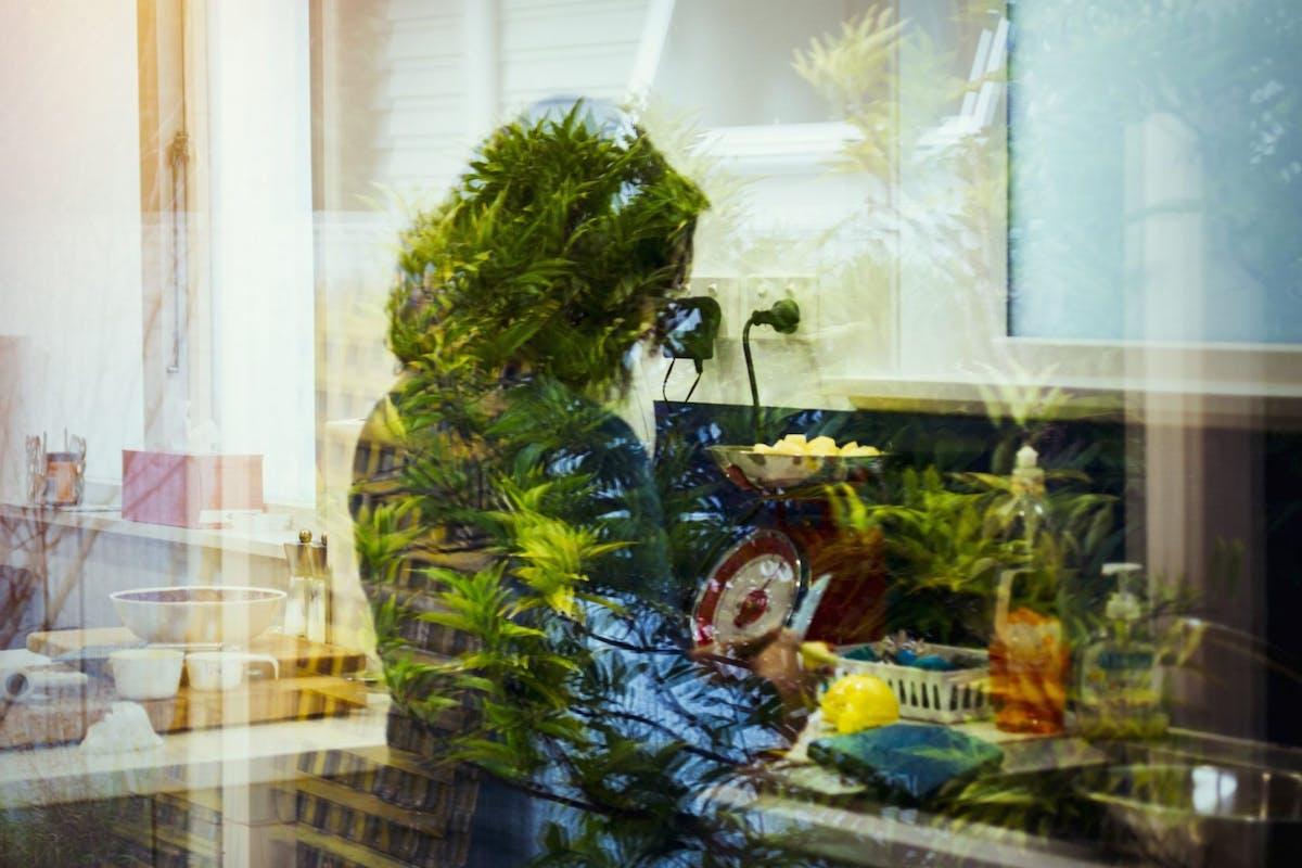 Mixed race woman behind window reflection