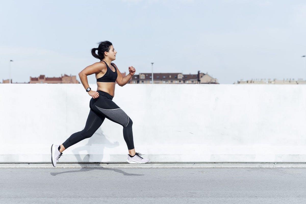 A woman running down an urban street in gray activewear