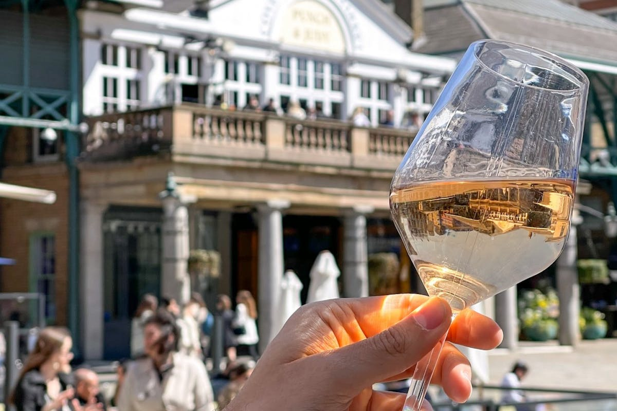 A glass of rose being held up in front of Covent Garden