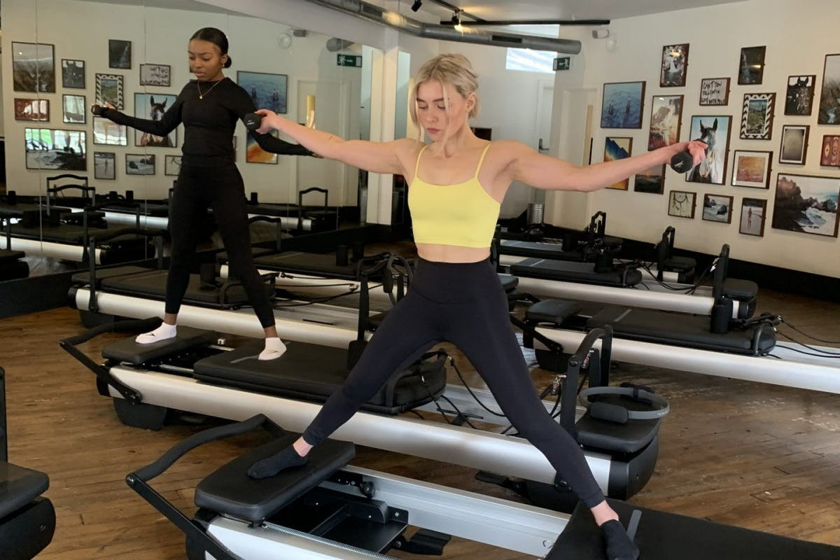 Chloe and Meeka on a reformer pilates class, doing a straddle pose and holding weights in their arms