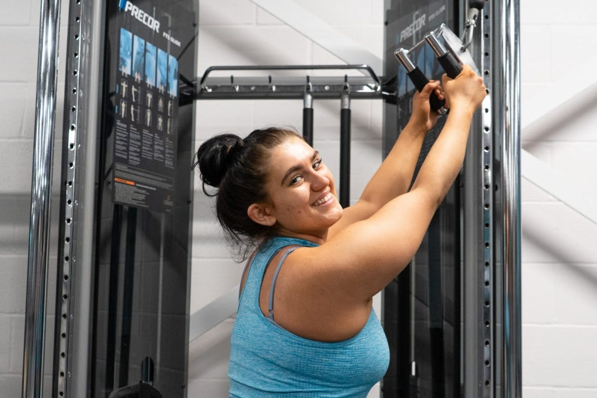 Sophie Butler wearing blue activewear pulling the cable machine handle above her head.