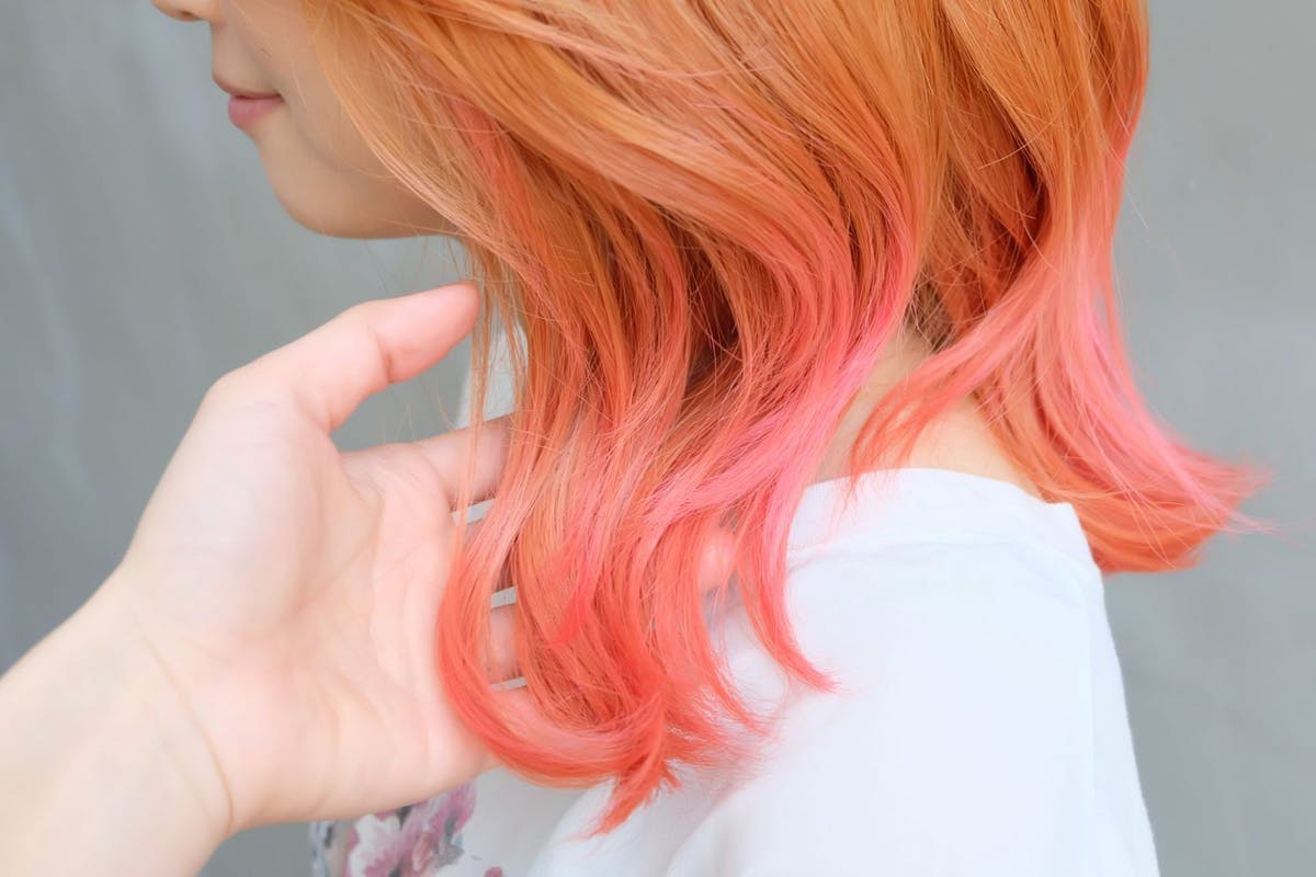 Portrait of a young woman with Blond - Pink Gradation Hair in front of a gray wall.