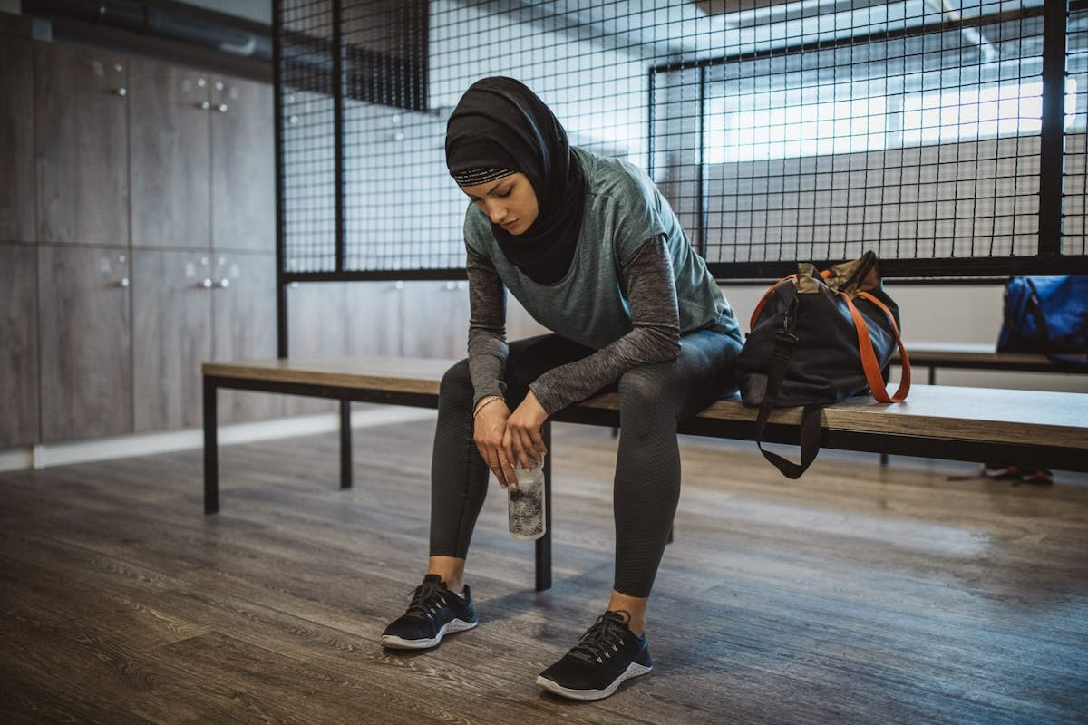 A woman sitting on a bench in a gym changing room with her head leaning forwards