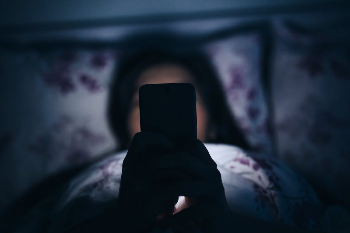 A woman scrolling on her phone in bed at night