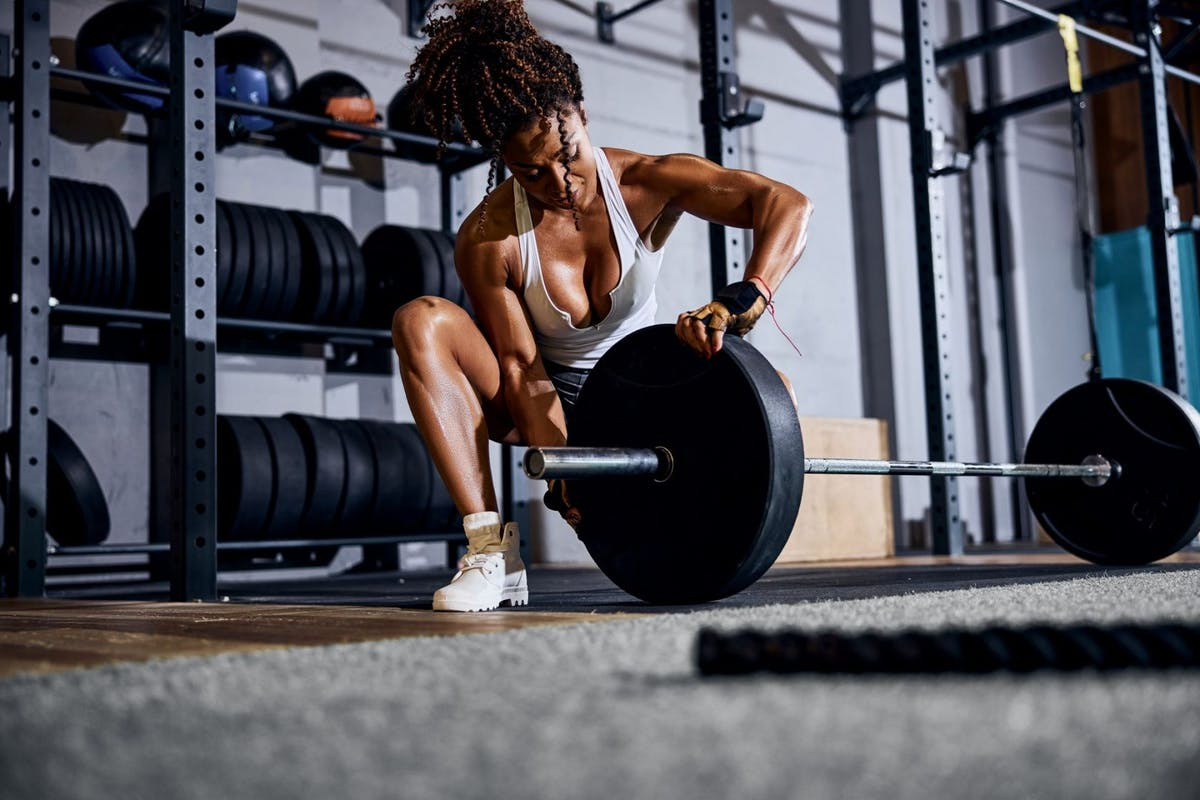 A woman in shorts and a crop top putting plates on a barbell