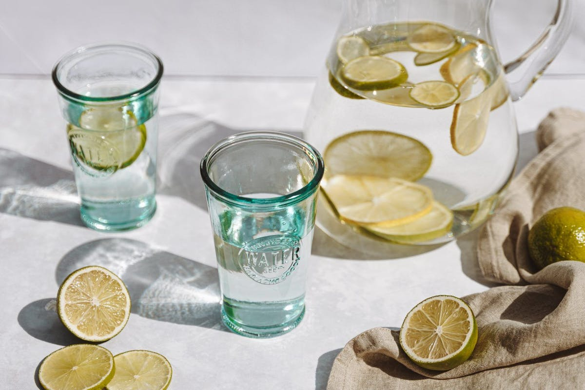 A jug of water with lemon in and glasses on a table.