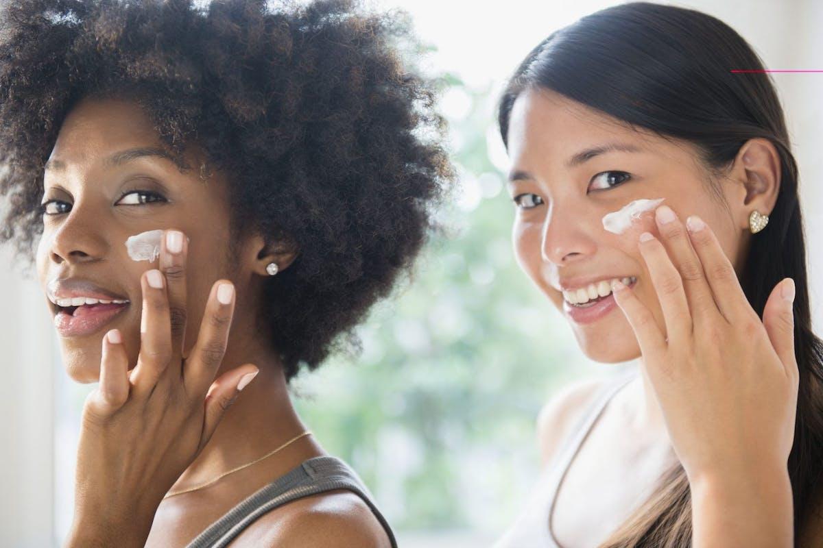 Two women applying moisturiser
