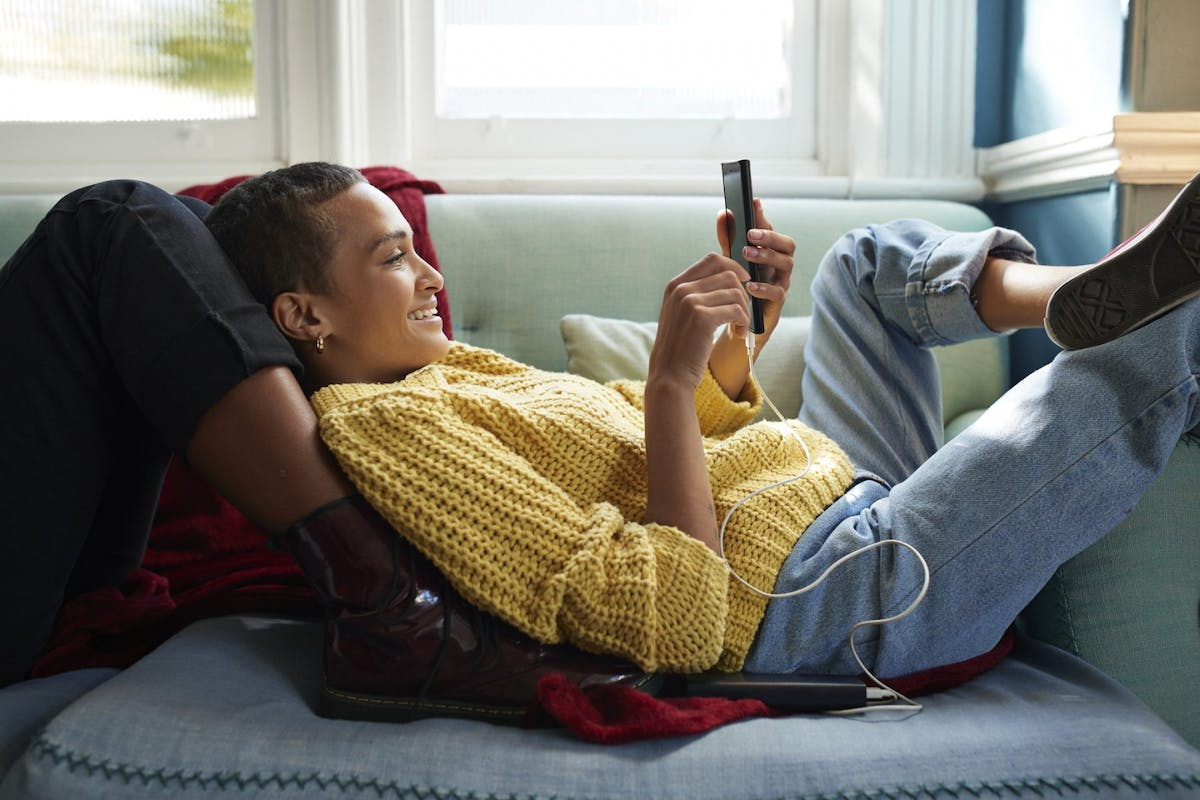 A woman lying on the sofa scrolling on social media