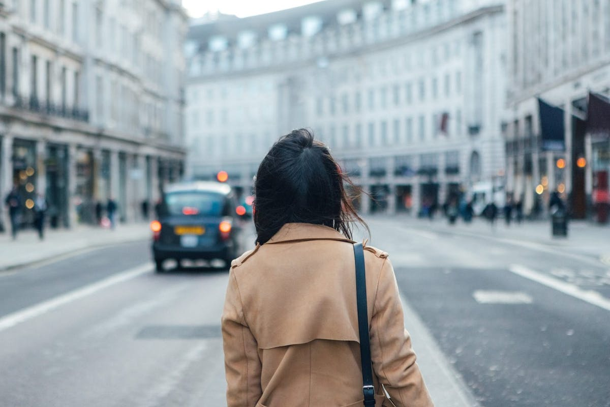 Woman with her back turned, wearing camel trench coat standing in the middle of central London street.