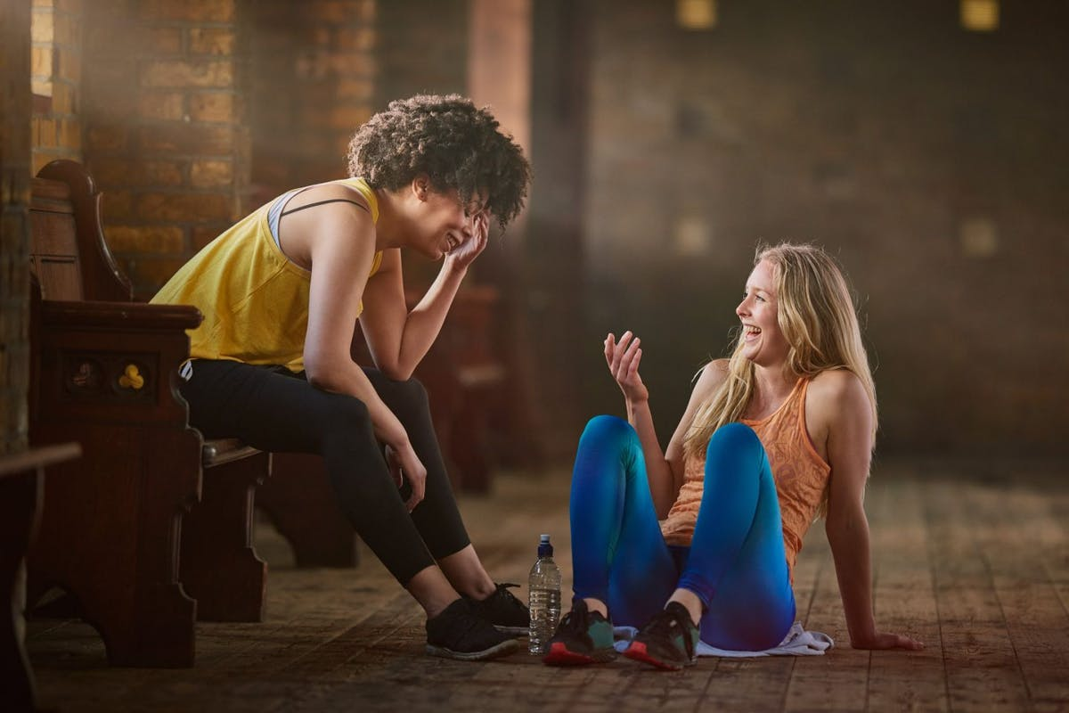 Two women in the gym sat on the floor laughing and talking to each other.