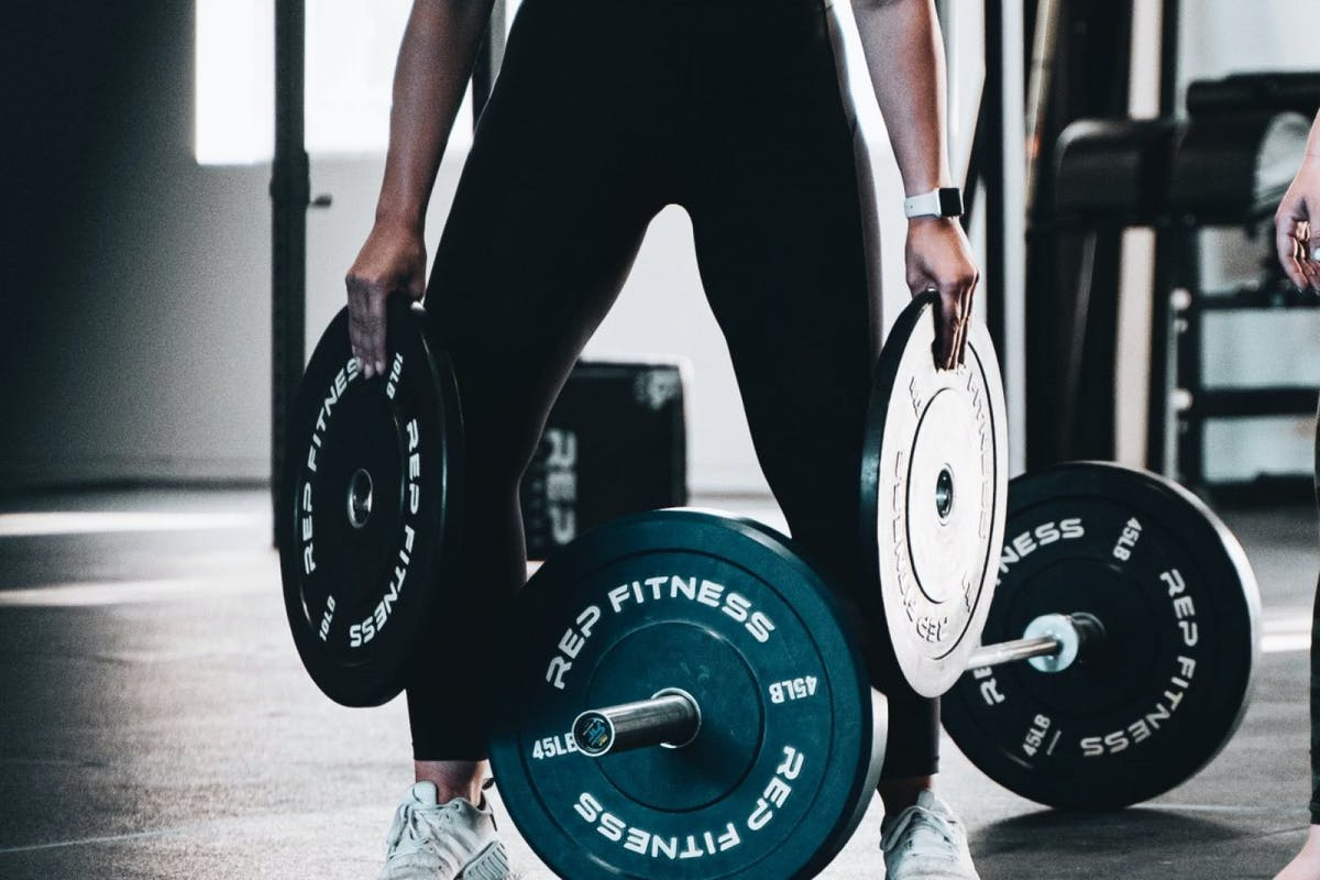A woman putting plates on a barbell.