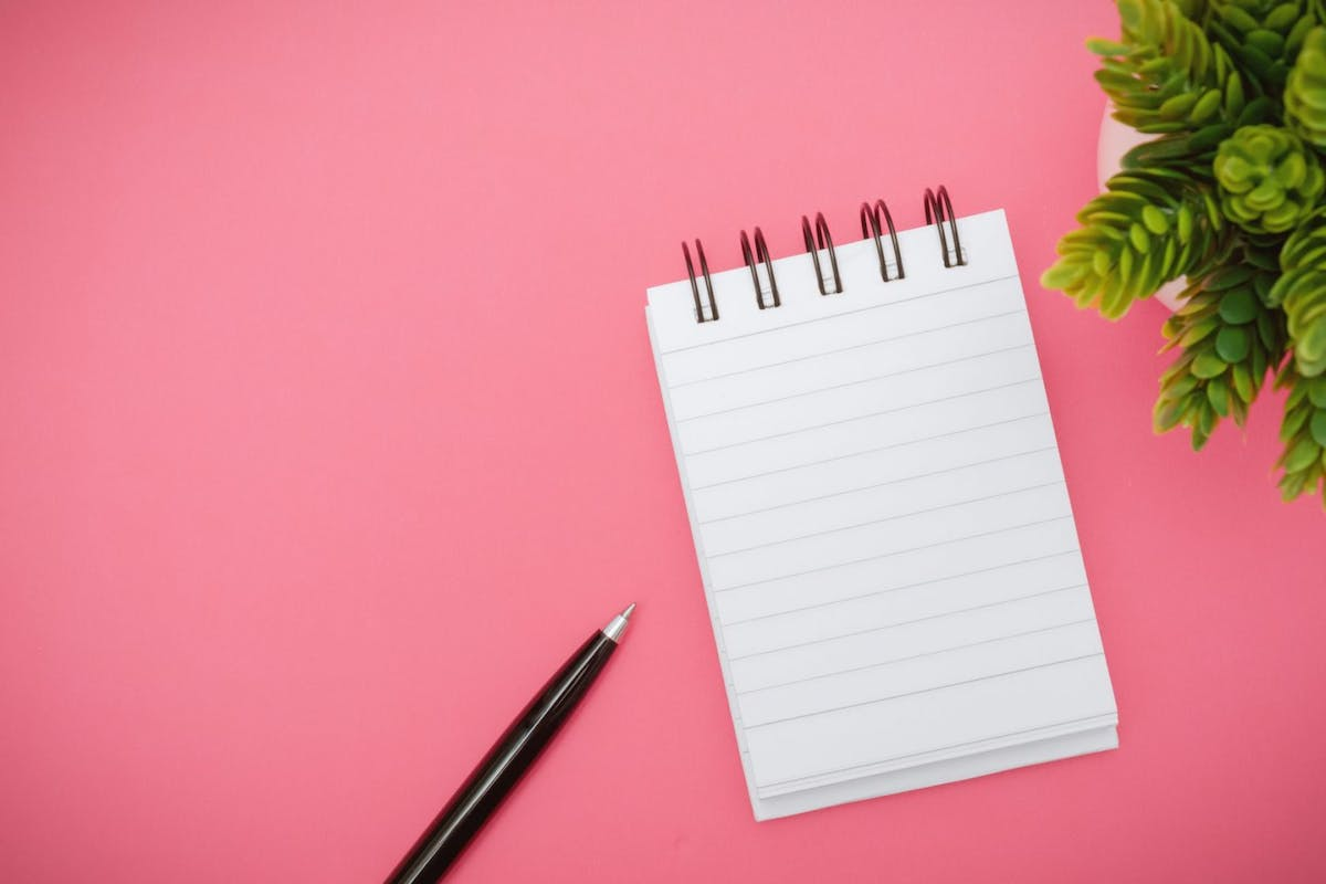 Notebook and pen on pink background