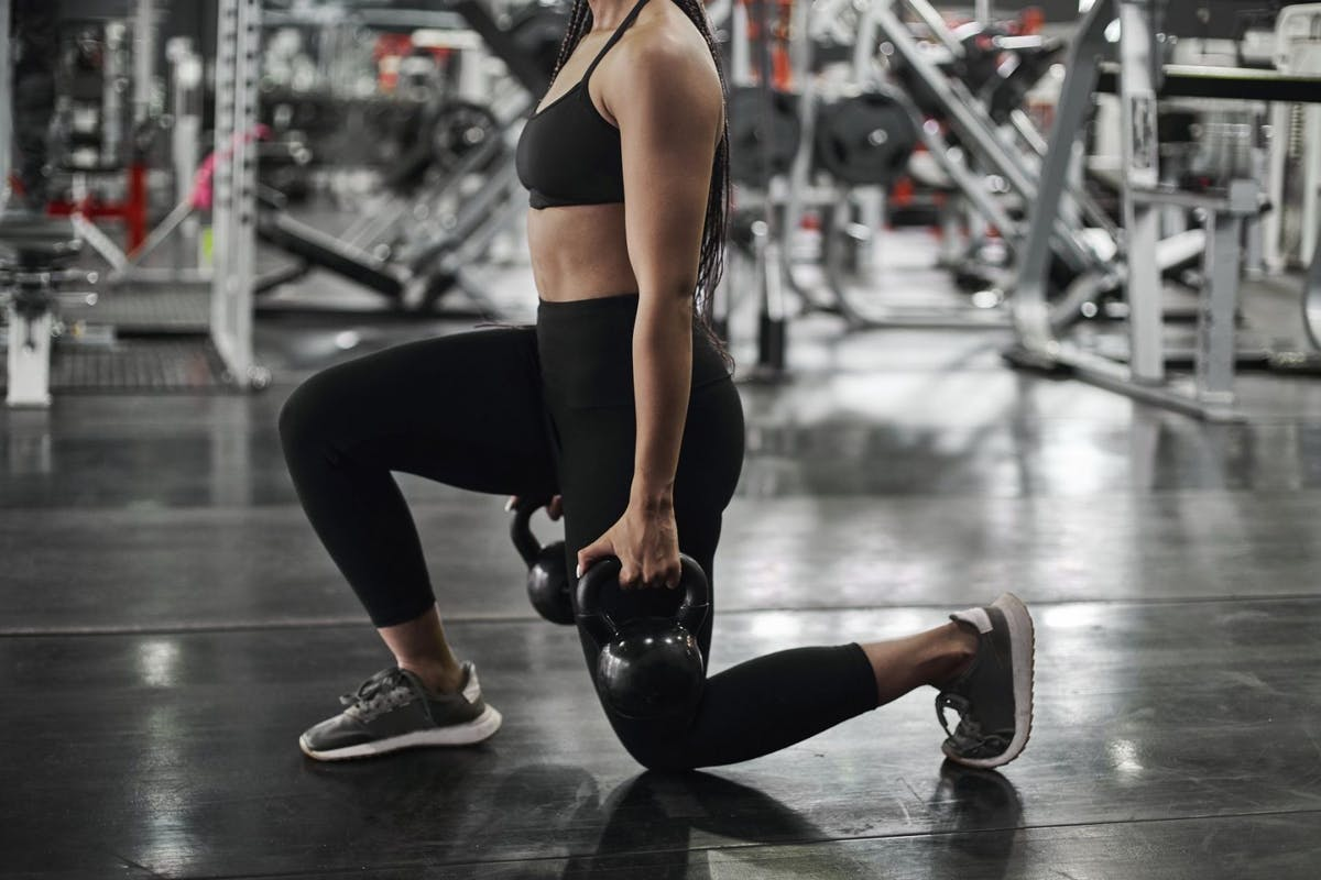 A woman doing a lunge with kettlebells in a gym.