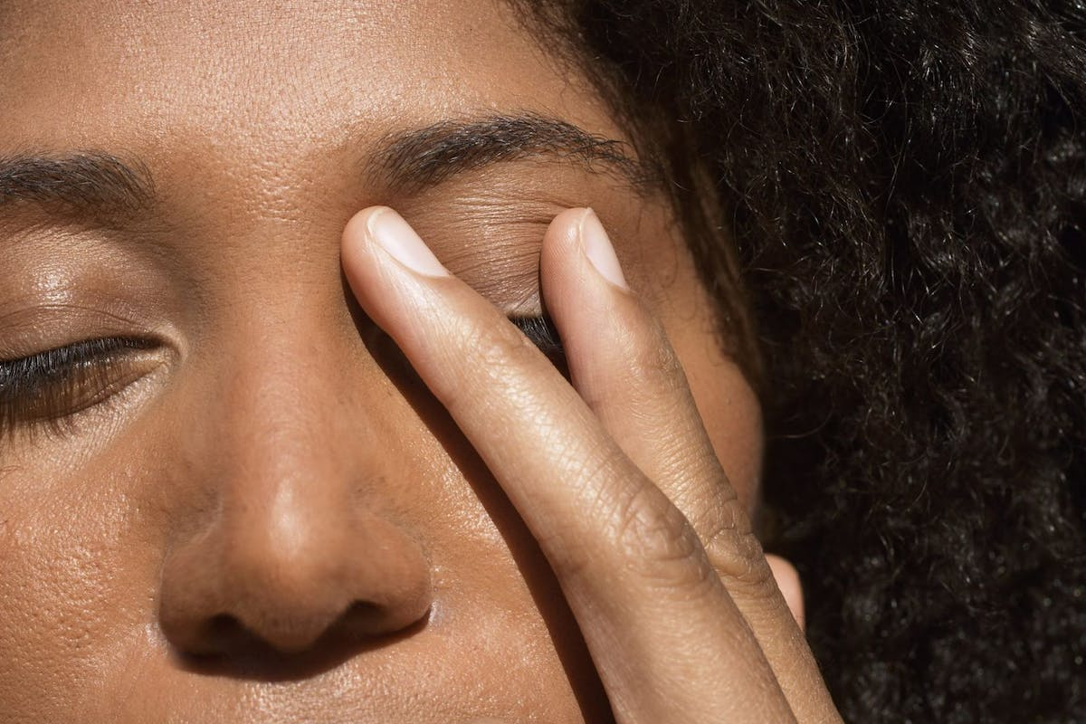 A woman doing tapping therapy by placing her fingers over her eyes.